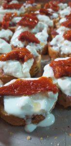Crostini con salsiccia, stracciatella di burrata e pomodori secchi